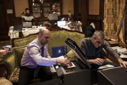 Dziennikarze sortują i kopiują dokumenty w salonie rezydencji Janukowycza Foto: Getty Images