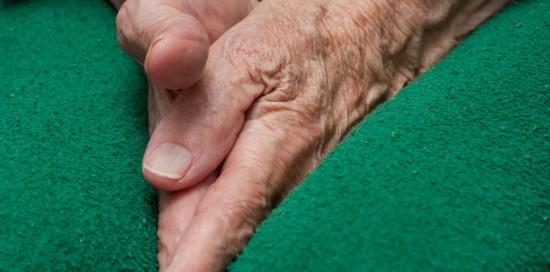 Old woman's hands tucked between her legs